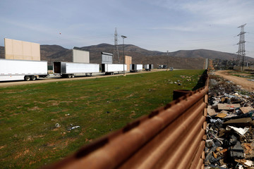 Prototypes for U.S. President Donald Trump's border wall with Mexico are shown blocked by trucks before Trump's visit to the area, in this picture taken from the Mexican side of the border, in Tijuana