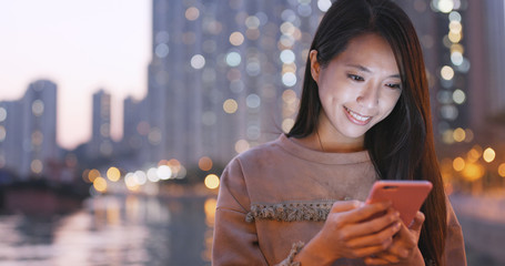 Wall Mural - Asian Woman use of smart phone in city at night