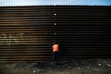 A boy looks through a hole in the current U.S.-Mexico border fence, in this picture taken from the Mexican side of the border in Tijuana