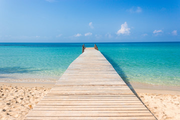 Wooden bridge on the tropical beach and blue sky