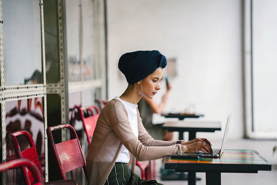 Portrait of a slim, young Muslim Malay woman sitting and working at a cafe during the day. She is wearing a turban and is fashionably dressed.