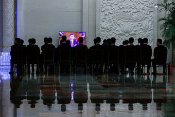 Chinese President Xi Jinping appears on screen as security officers and staff watch a live broadcast of the fourth plenary session of the National People's Congress at the Great Hall of the People in Beijing