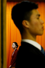 An attendant and a security officer stand at the entrance to the assembly hall during the fourth plenary session of the National People's Congress (NPC) at the Great Hall of the People in Beijing