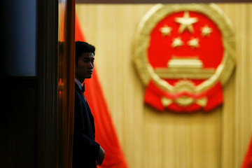 A member of the security staff keeps watch at the entrance to the assembly hall after the fourth plenary session of the National People's Congress at the Great Hall of the People in Beijing