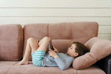 cute boy in casual clothes lying on the couch watching and playing tablet in the house
