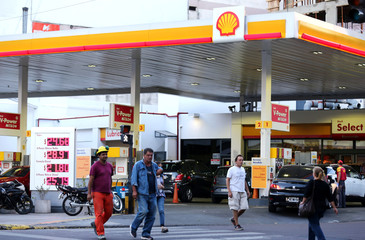 People walk in front of a Shell gas station in Buenos Aires