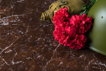 on a brown marble background military things and red flowers
