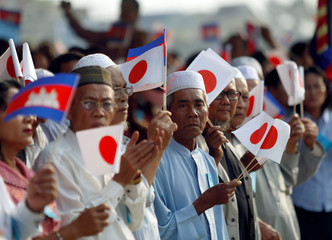 People hold Cambodian and Japanese flags during the inauguration ceremony of the road N.1 build with Japan aid in Phnom Penh