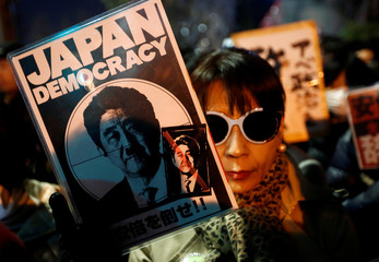 A protester holds a banner denouncing Japanese Prime Minister Shinzo Abe at a rally in Tokyo