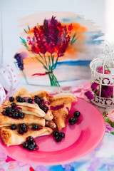 Breakfast: pancakes with blueberry berries, currants on a pink plate in the style of Provence.. dessert