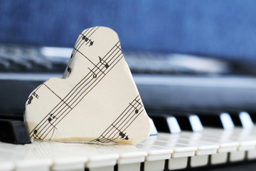 close-up music score on piano keyboard, heart of paper