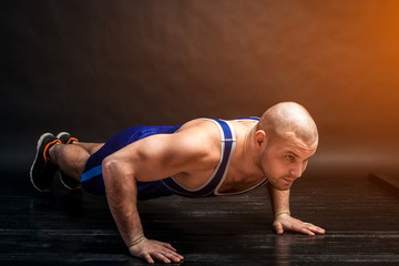 A young athletic man in blue wrestling tricky and blue shorts does push-ups on a black-haired isolated background in a photo studio