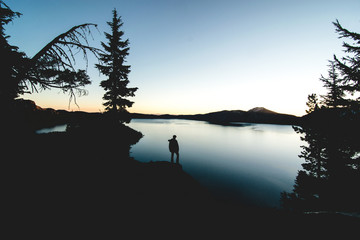 A lone figure stands on the edge of Crater Lake watching the sun rise