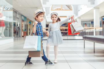 Group portrait of two cute adorable preschool children going shopping. Caucasian little girl and boy in mall. Kids holding shopping bags.