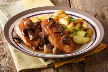 Italian American food: Chicken in Marsala wine with fried mushrooms and potatoes close-up. horizontal
