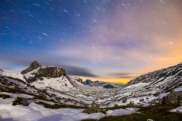 Wall Mural - Starry night sky in snowy alpine mountains. Winter in Swiss Alps, Switzerland.
