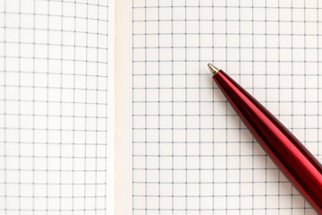 Open notebook with pen on white background closeup