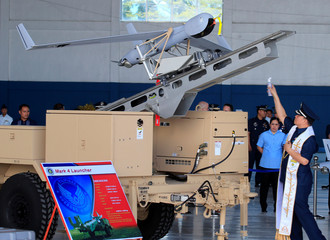 A Filipino army chaplain sprinkles holy water to bless a ScanEagle Unmanned Aerial Vehicle mounted at the Mark 4 launcher during a transfer from the U.S. to the Philippine Air Force at the Villamor Air Base in Pasay city