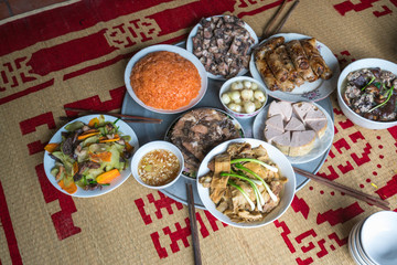 A traditional Vietnamese meal for lunar new year Tet holiday in spring, placed on new flowered sedge mat, on the last day of the last year