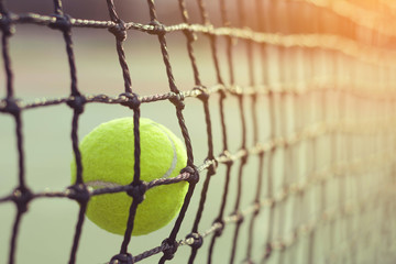 Close up tennis ball hitting to net on blur background