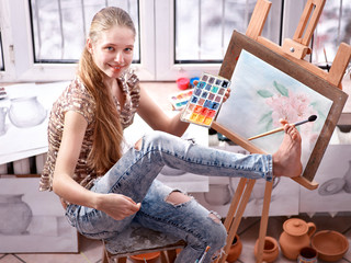 Artist painting on easel in studio. Self-expression of authentic girl paints with brush in morning sunlight dawn light toning. Drawing school picture with your foot. How to draw with your feet.