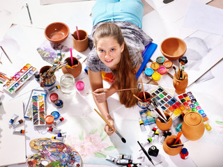 Authentic artist children girl paints with set palette watercolor paints palette and brush in morning sunlight. Painting in studio on floor. Top view art workshop for talented child.