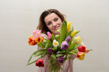 Young charming girl with a bouquet of flowers - multi-colored tulips