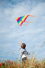 happy caucasian little boy standing among grass holding flying colorful kite on blue sky background