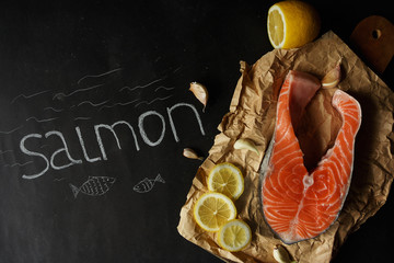 """Juicy salmon steak on kraft paper. Black background. The inscription """"salmon"""" with white chalk. Place for your text"""
