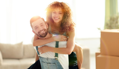 wife hugs her husband in a new apartment.
