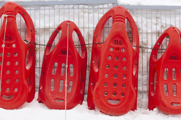 Red sledges ready to rent. Winter sports. Recreation