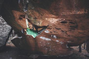 Rock climber climbing a steep roof boulder problem