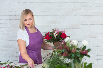 Beautiful young woman florist makes a nice bouquet with different flowers in own flower shop