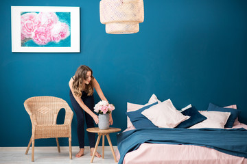 Young woman decorating bedroom with beautiful flowers at home Fototapete