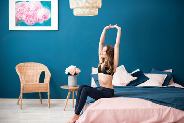Young woman in bra sitting on the bed raising up hands in the cozy bedroom at home
