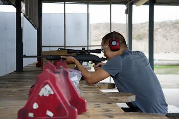 Asian man shooting rifle at shooting range