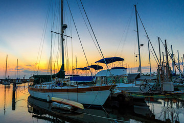 Small vessels docked at Ala Wai Boat Harbor in Honolulu, Hawaii at sunset