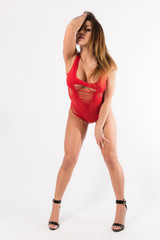 Young fit hispanic woman in red one piece and black high heels posing on a white background