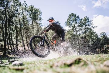 Male cyclist splashing water with mountain bike Fototapete