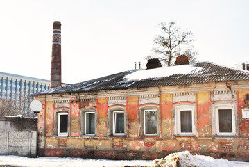 Old red brick pipe with white ornaments, residential district with shabby pink house and administrative building on background, winter snowy streets with trees, horizontal