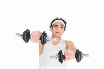 Wall Mural - Portrait of skinny young man in sportswear holding dumbbells isolated on white