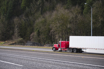 Big rig classic red semi truck with refrigerator semi trailer running on the wide road with trees on the background