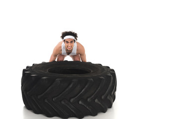 Wall Mural - Young skinny sportsman raising tire of wheel isolated on white