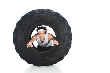 Wall Mural - Thin sportsman with headband inside tire of wheel isolated on white