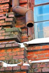 Rusty drain pipe along window corner on red  brick wall, snow on window sill, grunge texture background,