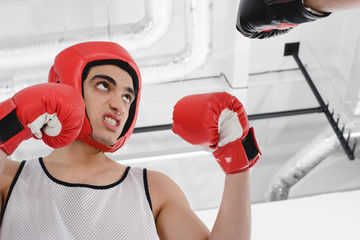 Wall Mural - Low angle view of angry skinny sportsman in boxing helmet and gloves