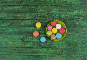 colorful french macarons ,green wooden table