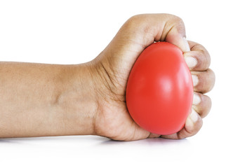 Hand squeezing red stress ball on white background