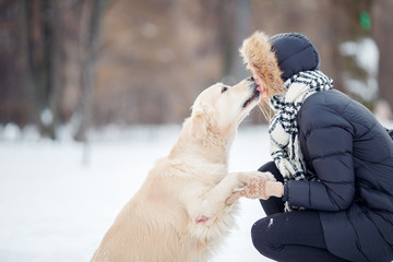 Picture of girl hugging labrador in snowy park