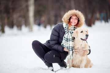 Picture of girl in black jacket squatting next to dog in winter